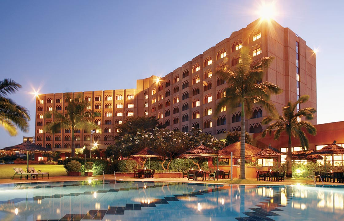 The Dar Es Salaam Serena Hotel in Tanzania at dusk above a swimming pool with palm trees surrounding it
