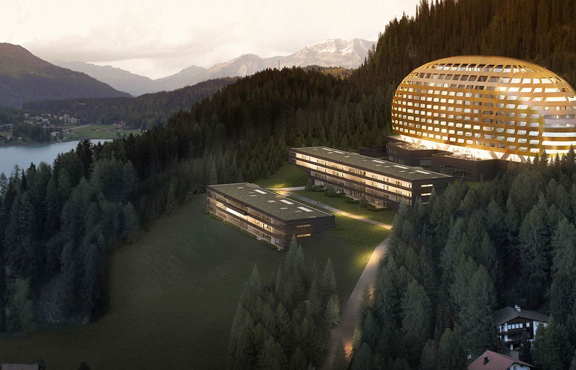 The InterContinental hotel Davos in Switzerland lit up at night in front of a scenic mountain range