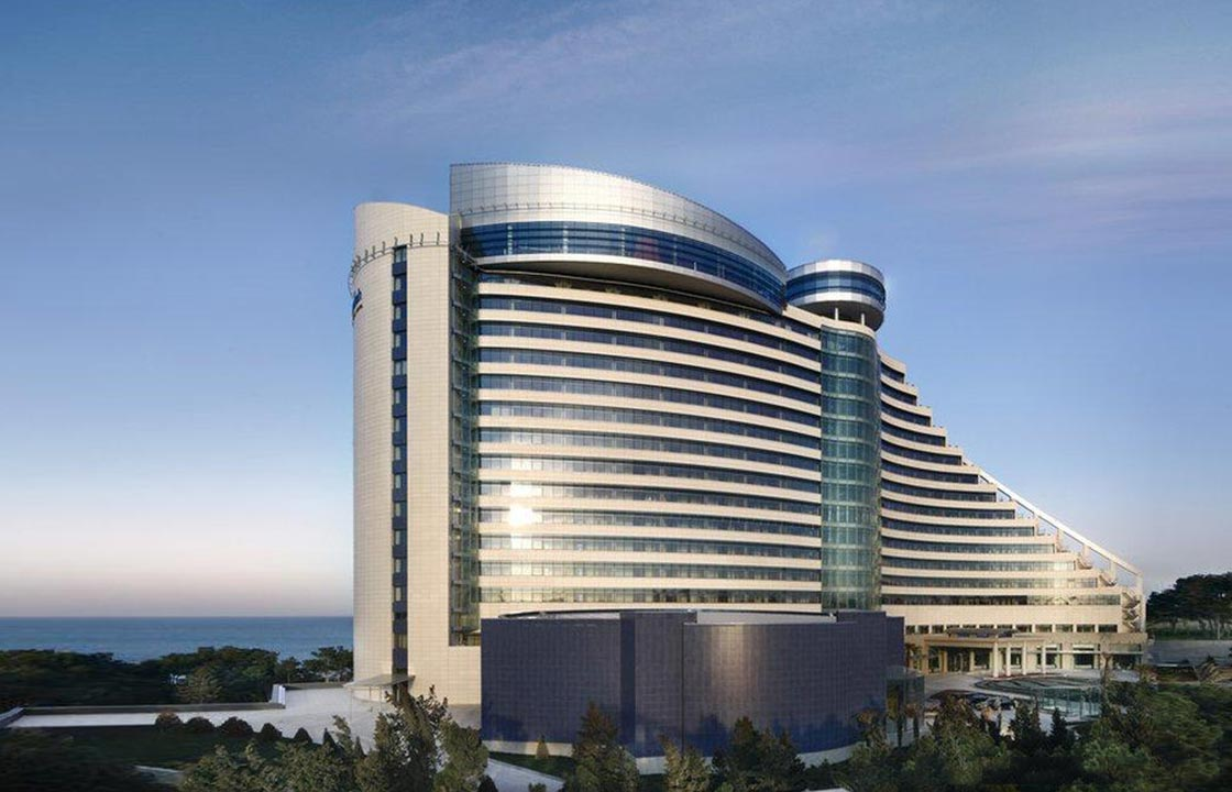 The jumeirah bilgah beach hotel with a sea view at sunset