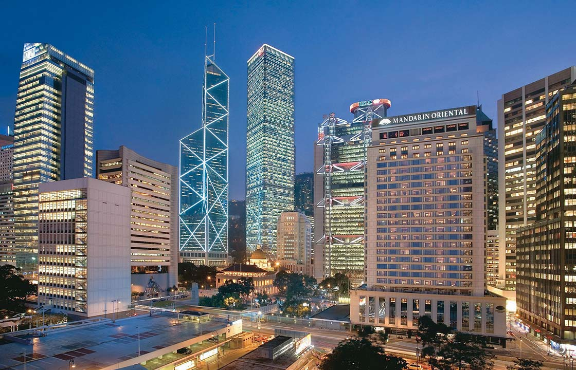 The Mandarin Oriental Hotel Hong Kong at night surrounded by other hotels and busy streets