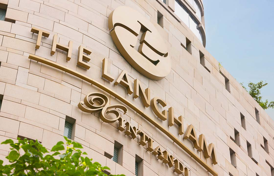 The gold sign of the Langham Hotel Shanghai China on the side of the hotel