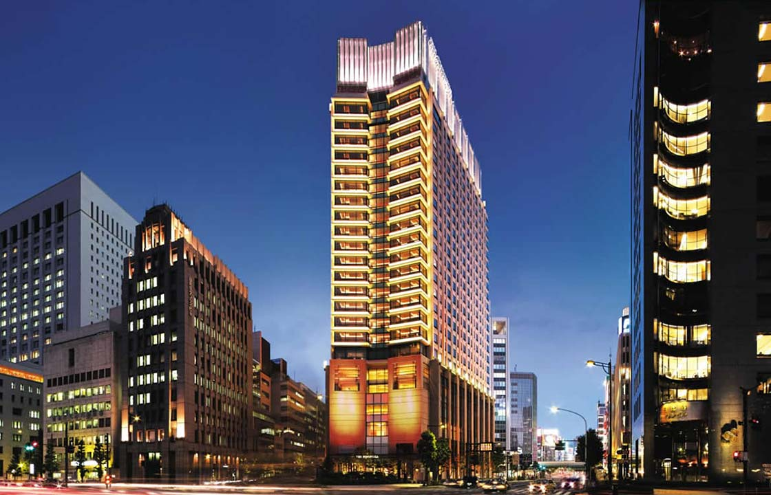 The Peninsula Hotel in Tokyo Japan lit up at night next to other hotels above a busy street