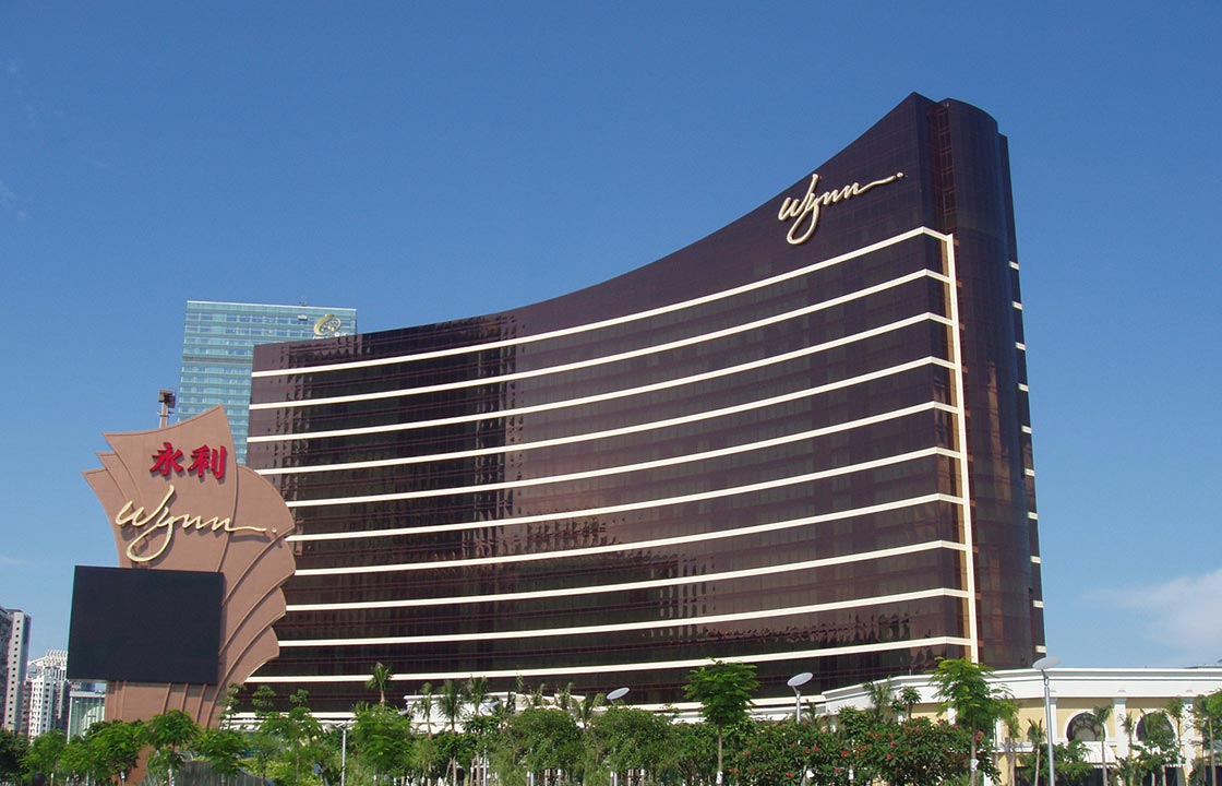 the wynn macau hotel in china standing above green trees at its base