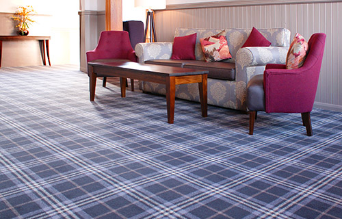 Hotel waiting room with a blue and white checked flooring, a sofa and a wooden coffee table