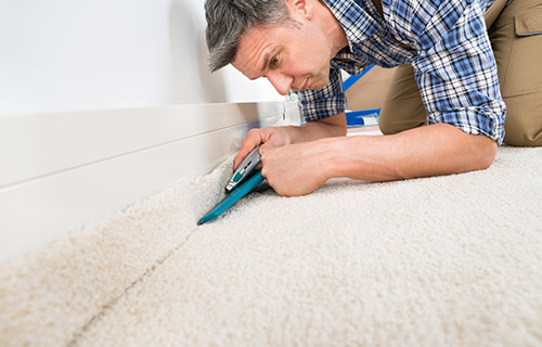 A carpet fitter in a blue shirt cutting a cream carpet with a high quality underlay to size with a Stanley knife