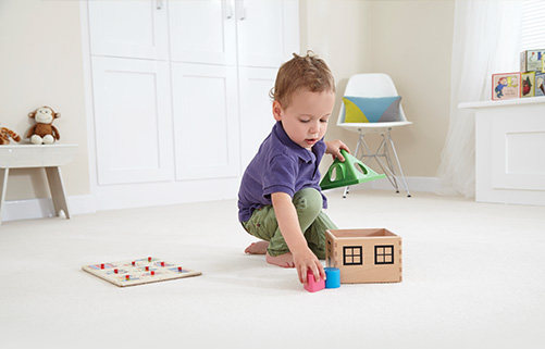 A toddler playing with his toy house on a floor fitted with an extra comfortable underlay