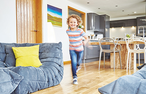 Toddler running through a living room fitted with a sound reducing underlay