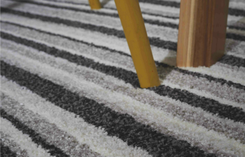 a light brown wooden chair leg on a striped black and white carpet with a good underlay